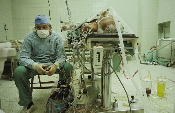 Ahli bedah Zbigniew Religa usai menyelesaikan operasi transplantasi jantung selama 23 jam. Dirinya duduk dengan wajah cemas mengawasi tanda vital pasien sementara asistennya beristirahat di lantai. Foto: National Geographic