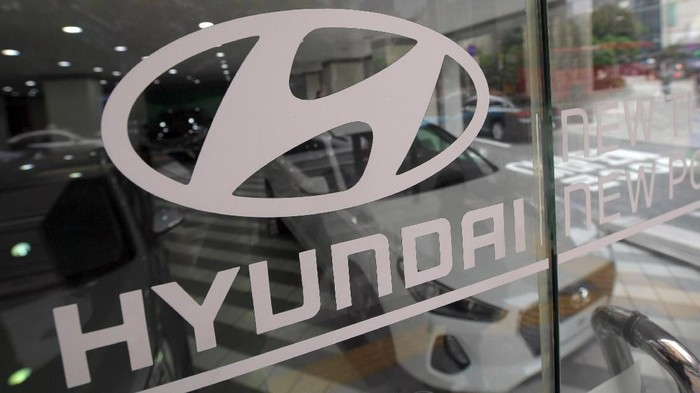 The logo of Hyundai Motor is seen on a glass door at a dealership in Seoul on October 26, 2016. South Koreas Hyundai Motor on October 26 announced a sharp fall in profits for a third quarter, hit by lengthy industrial action that also took a toll on the national economy.  / AFP PHOTO / JUNG YEON-JE