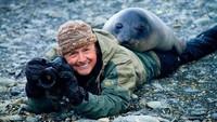 Foto: Sudah pergi jauh-jauh, dingin pula, eh singa laut yang ingin difoto malah terlanjur akrab dengan si fotografer. Seperti bapak dan anak yang lagi mainan ya? (Twitter/@polychromantium)
