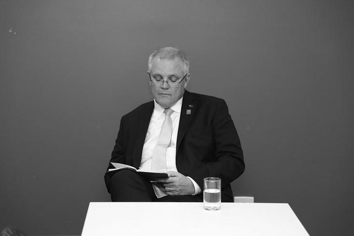 Dalam foto berlatar hitam putih ini, Morrison sedang santai sambil membaca buku. Segelas air putih siap membilas tenggorokan saat haus melanda. Foto: Istimewa