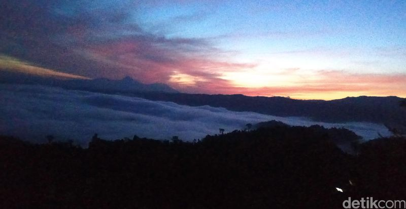 Cahaya oranye di balik gumpalan awan tebal di puncak Gunung Payung memang cantik. Serasa kita berada di negeri awan. (Michelle de Jonker/detikTravel)