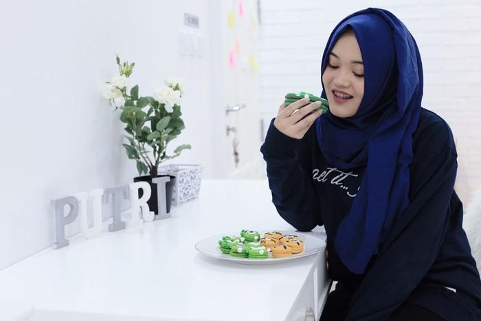 Pemilik nama lengkap Putri Delina Andriany Sutisna ini pencinta sajian manis. Lihat saja gayanya saat melahap macaron bertema Monster Inc dan Minion ini. Foto: Instagram putridelinaa