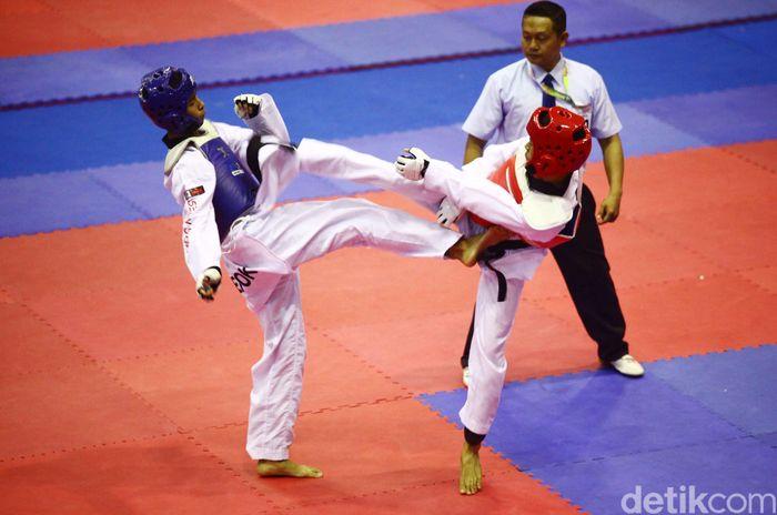 Dua orang atlet saling serang untuk menjatuhkan lawan.