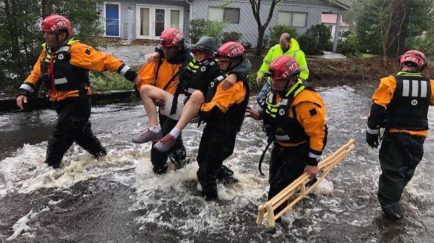 Petugas menolong seorang pria yang terkena banjir akibat badai Florence, Carolina Utara, AS, 14 September.