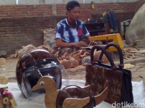Mengolah batok kelapa menjadi barang seni.