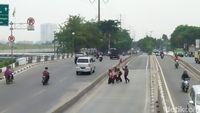 Tukang ojek membantu siswa SD menyebrangi jalan raya. Kondisi ini sangat membahayakan keselamatan