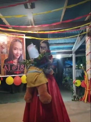 Aljean Degamon Legaspino dansa dengan boneka yang ditempel foto ayahnya di pesta ulang tahunnya