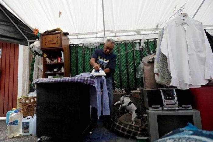 Seorang warga Meksiko Enrique Alcantara sedang menyetrika pakaiannya di tenda pengungsian yang dibuat untuk korban gempa dashyat di Meksiko. Reuters/Henry Romero.