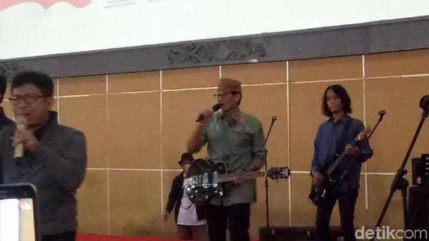 Aksi Sandiaga bermain alat musik.