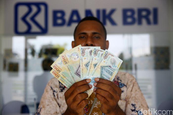 Petugas BRI memperlihatkan mata uang Kina di loket money changer di kawasan PLBN Skouw.