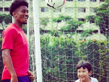 Aih senangnya seorang anak diajarimemasukkan bola ke gawang lewat sundulan kepalaoleh pemain Arsenal. (Foto: Instagram @arsenal)