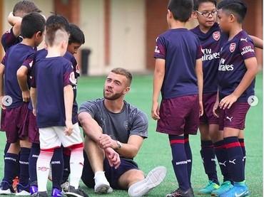 Anak-anak yang sedang berlatih semangat banget mendengarkan nasihat pemain Arsenal. (Foto: Instagram @arsenal)