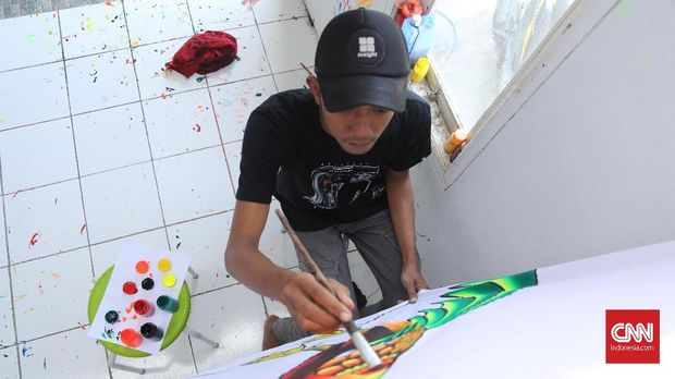Trisno, pelukis spanduk pecel lele Lamongan mempertahankan teknik melukis.