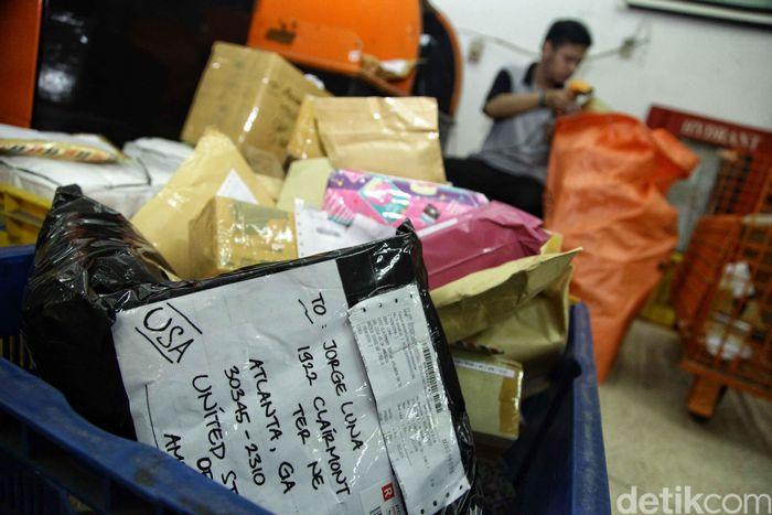 Seorang pegawai tampak menyortir surat ke dalam kantung yang hendak di ekspor ke luar negeri.