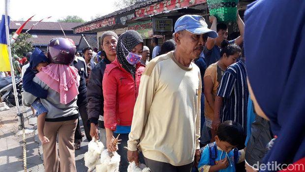 Warga membawa ayam hidup yang dibagikan gratis oleh peternak