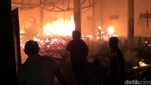 Api muncul dari salah satu gudang yang kemudian menyambar ke gudang lain