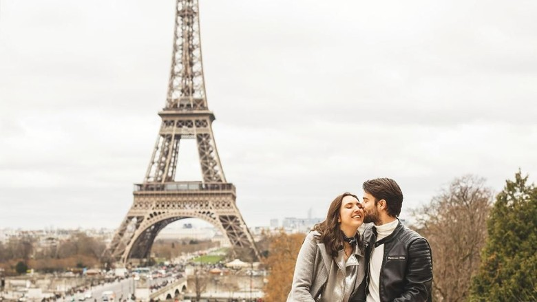 Young couple sitting on surrounding wall with a view on Eiffel tower, the symbol of France. The man kisses his girlfriend on the cheek.