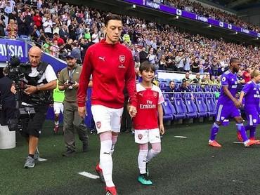 Wah digandeng pemain Arsenal Mesut Ozil pastinya anak ini senang banget ya. (Foto: Instagram @juniorgunners)