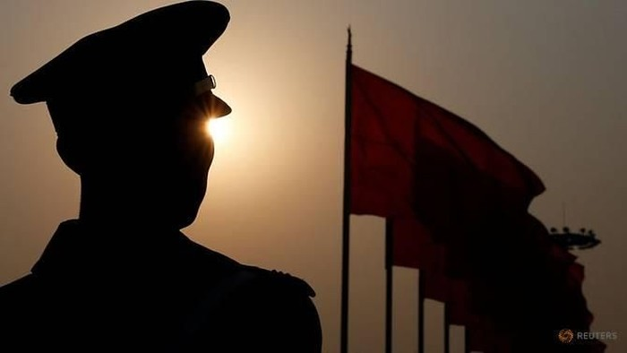 File photo: A paramilitary police officer is seen silhouetted in front of flags. (Photo: REUTERS/Aly Song)