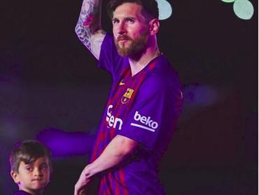 Lionel Messi menggandeng seorang anak. Lihat apa sih, Nak? (Foto: Instagram @fcbarcelona)