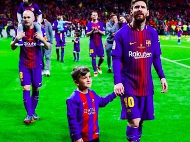 Lihat, ada yang senyum-senyum sendiri saat digandeng kelapangan hijau sama pemain Barcelona Lionel Messi nih, he-he-he. (Foto: Instagram @fcbarcelona)