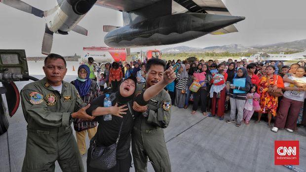 Warga histeris saat mencoba mengevakuasi diri dari Palu dengan pesawat Hercules di Bandara Mutiara Sis Al Jufri Palu, Sulawesi Tengah, Minggu (30/9).
