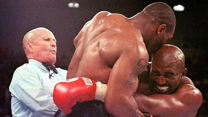 Referee Lane Mills (L) steps in as Evander Holyfield (R) reacts after Mike Tyson bit his ear in the third round of their WBA heavyweight championship fight at the MGM Grand Garden Arena in Las Vegas, NV 28 June. Holyfield won by disqualification after the biting incident.     AFP PHOTO/JEFF HAYNES / AFP PHOTO / JEFF HAYNES