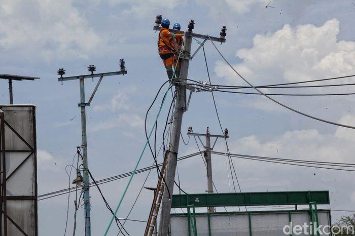 Beberapa petugas memanjat tiang listrik untuk memperbaiki jaringan yang rusak akibat gempa bumi.