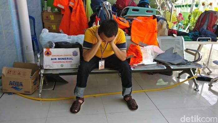 dr Agung dari RSUD Koja tampak kelelahan dan beristirahat sejenak di samping kardus bantuan air mineral. Foto: Firdaus/detikHealth