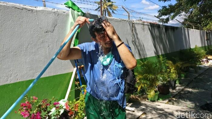 Spesialis ortopedi dr Arsanto kewalahan dengan panas di Palu yang menyengat. Ia langsung menyiram dirinya dengan air usai mengoperasi pasien patah tulang akibat gempa. Foto: Firdaus/detikHealth