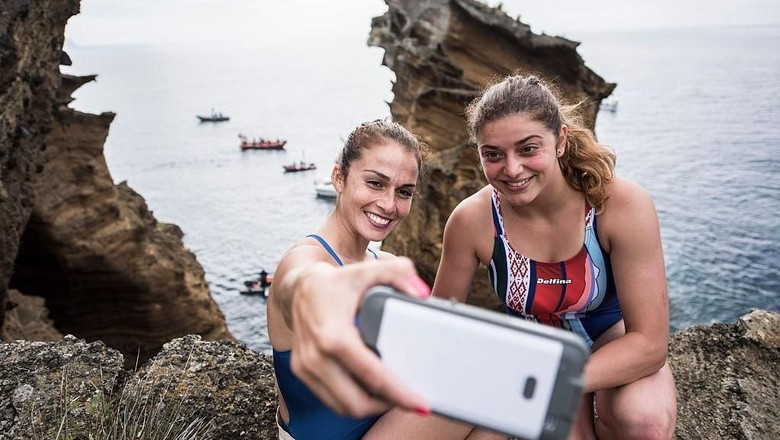 AZORES, PORTUGAL - JULY 07:  (EDITORIAL USE ONLY) In this handout image provided by Red Bull, Jacqueline Valente (L) of Brazil takes a selfie with Yana Nestsiarava of Belarus on the cliffs at Islet Franca do Campo during the first training session prior to the third stop of the Red Bull Cliff Diving World Series, Sao Miguel, Azores, Portugal on July 7th 2016. (Photo by Dean Treml/Red Bull via Getty Images)