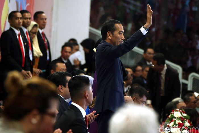 Jokowi melambaikan tangan saat tiba di lokasi.