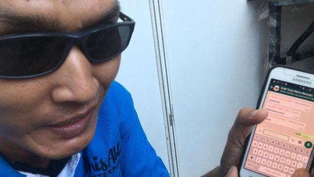 Ridwan, salah satu tuna rungu juru pijat Asian Para Games 2018, amat mengandalkan telepon pintar untuk komunikasi. (