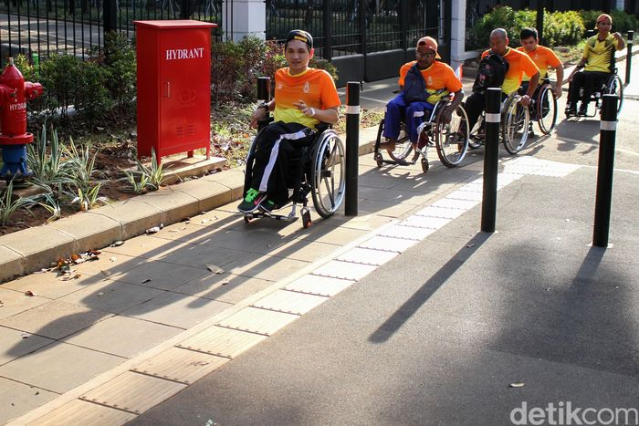 Sejumlah suporter Asian Para Games 2018 melintas di trotoar yang telah dilengkapi dengan jalur khusus penyandang disabilitas.