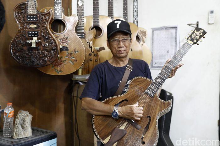 I Wayan Tuges berpose dengan gitar yang telah diukirnya.