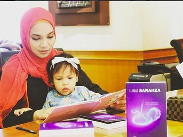 Sarahza menemani Bunda Hanum Rais membaca nih. Memang, banyak membaca banyak ilmu ya, Nak. (Foto: Instagram @hanumrais)
