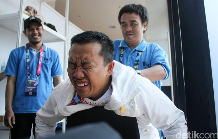 Begini ekspresi Menpora Imam Nahrawi saat coba fasilitas pijat gratis di GBK Arena, Jakarta, Jumat (12/10/2018).