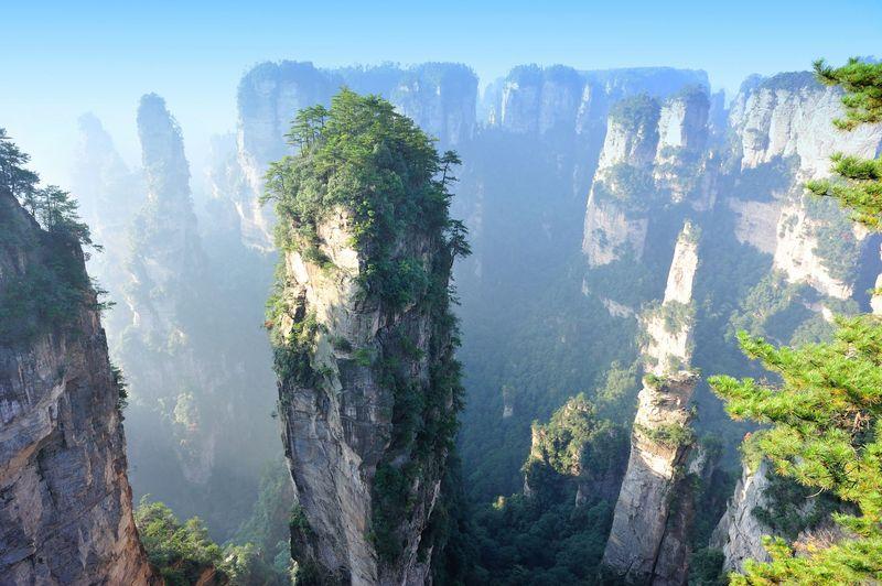 Inilah perbukitan batu di Zhangjiajie, China. Saat cuaca berkabut, wisatawan akan melihat ilusi mata seolah bukit-bukit di sana terlihat melayang (iStock)