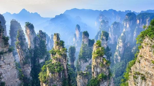 Beginilah perbukitan batu yang ada di Zhangjiajie, China. Saat cuaca berkabut, wisatawan akan terilusi pemandanganyan sehingga membuat bukit-bukit di sana terlihat melayang. Istimewa/iStock