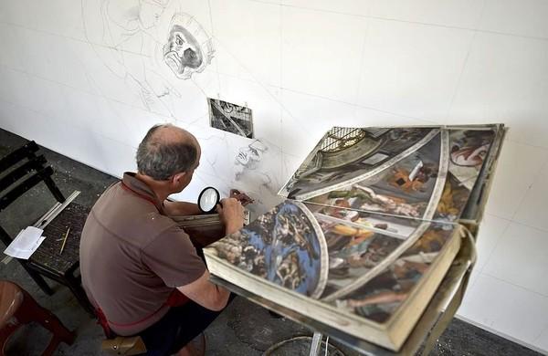 Dengan dibantu 2 orang asisten, Miguel membuat lukisan ini per bagian di atas kanvas. Total ada 14 kanvas untuk membuat lukisan ini (AFP/Getty Images)