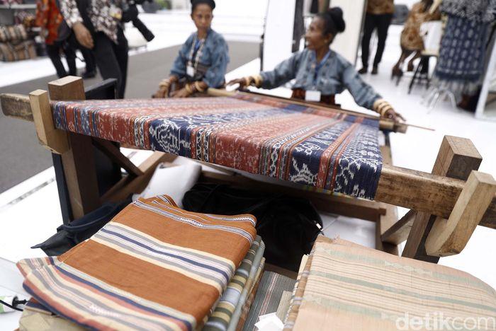 Seorang perajin asal Maumere NTT mempraktekkan cara menenun kain.
