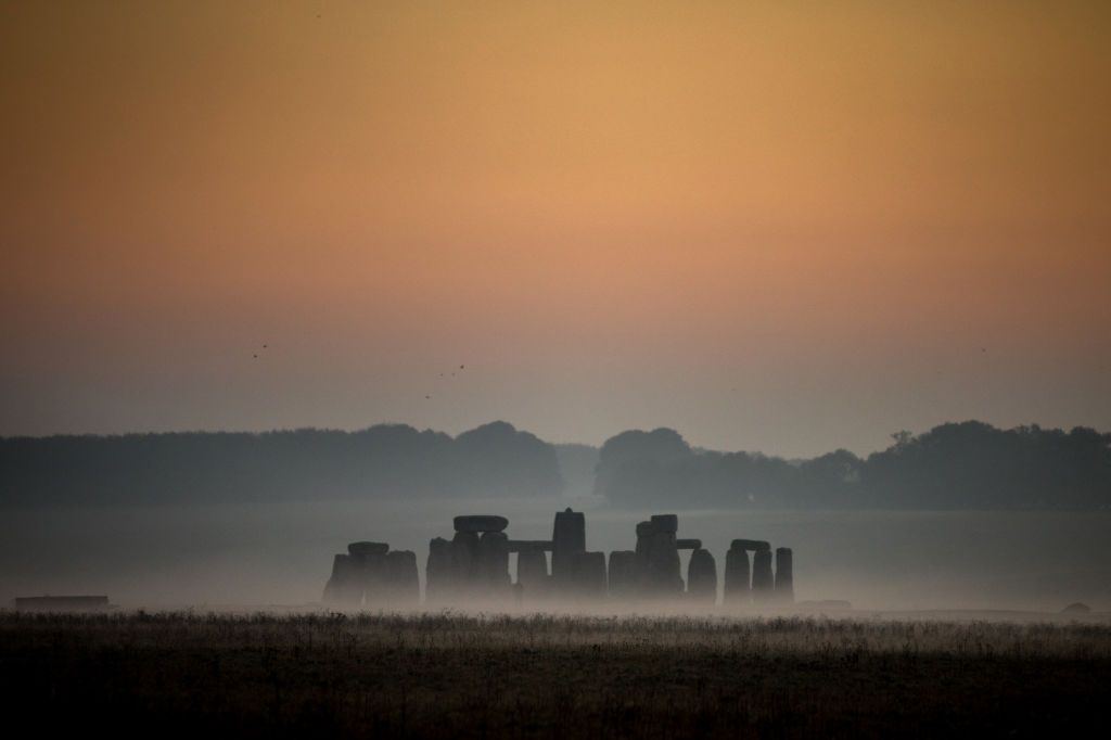 STONEHENGE, ENGLAND - OCTOBER 10:  Mist surrounds the stones at Stonehenge near Salisbury as dawn breaks on October 10, 2018 in Wiltshire, England. Many parts of the UK are experiencing temperatures almost 10C higher than average which could see the hottest October day for many years. However, the settled weather is forecast to be replaced by much more wet and windy conditions at the weekend, forcing the Met Office to issue weather warnings, as the UK braces itself for Storm Callumwith 80mph winds and 120mm of rain. (Photo by Matt Cardy/Getty Images)