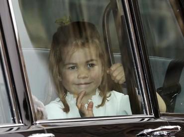 Seperti biasa, Putri Charlotte paling ramah dan rajin menyapa dari dalam mobil. (Foto: Alastair Grant - WPA Pool/Getty Images)