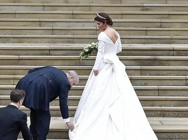 Sang ayah dengan senang hati membenarkan gaun putrinya. So sweet! (Foto: Toby Melville - WPA Pool/Getty Images)