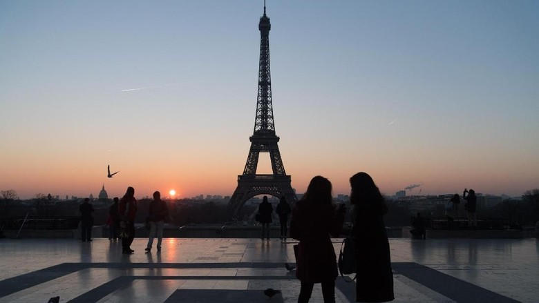 PARIS, FRANCE - JANUARY 18:  Tourists stand in front of the Eiffel tower at sunrise on January 18, 2017 in Paris, France.  (Photo by Pascal Le Segretain/Getty Images)
