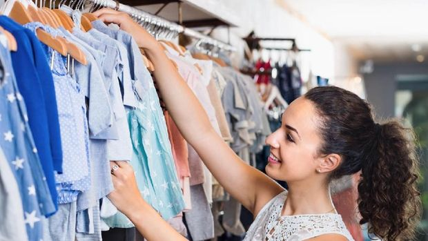 Young cheerful woman choosing blue baby clothes in kids apparel boutique