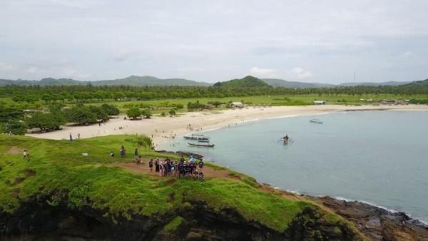 Di sebelah timur Bukit Merese ada Pantai Tanjung Aan. Pasir putih menghampar di garis pantai yang melengkung seperti bulan sabit ini. Ayunannya jadi favorit wisatawan (Fraga Tanansyah/dTraveler)