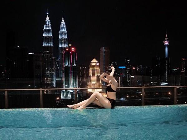 Saat sedang senggang, Mabel suka berenang di Kuala Lumpur. Itu tampak dari Menara Kembar Petronas yang jadi latar belakang foto Mabel. (Instagram/@mabel_goo)