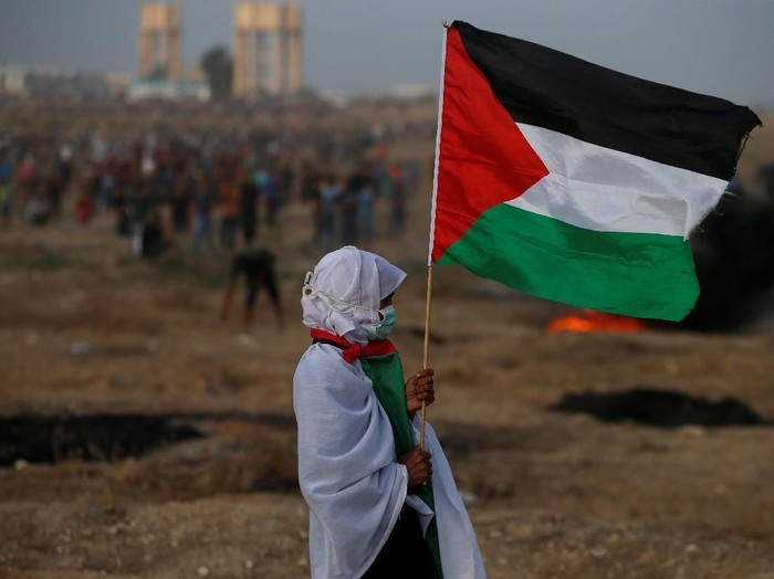 A woman holds a Palestinian flag during a protest calling for lifting the Israeli blockade on Gaza and demanding the right to return to their homeland, at the Israel-Gaza border fence in Gaza October 19, 2018. REUTERS/Mohammed Salem