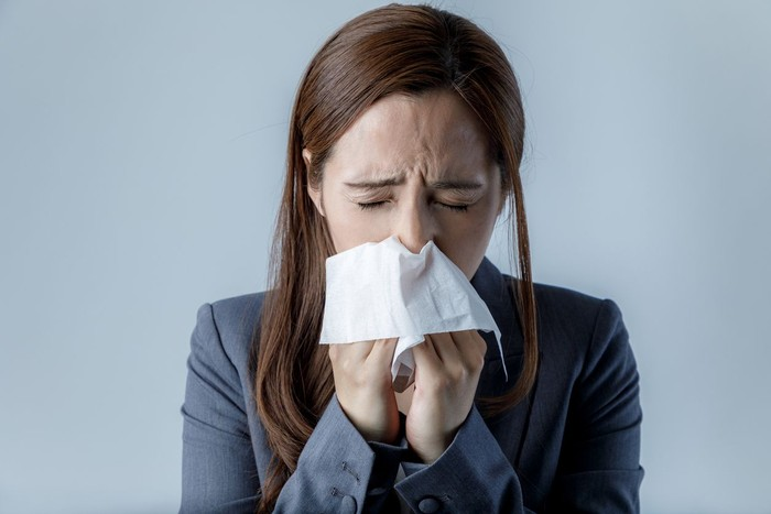 Sick Woman Sneezing in to Tissue Paper